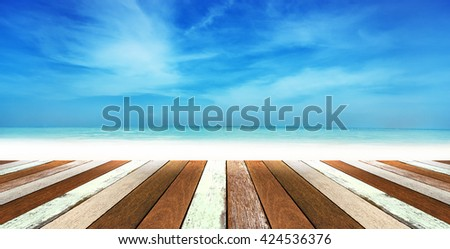 Wood table top with blurred nature scene tropical beach and blue sky