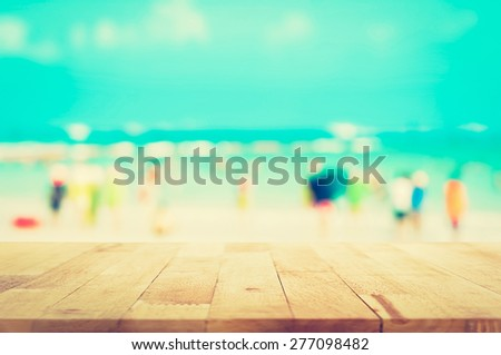 Wood table top with blurred people at the beach as background in vintage tone - can be used for display or montage your products - stock photo
