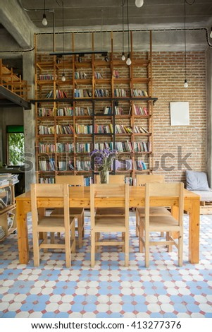 wood table with book shelf ,Home library with arm chair. Clean and modern decoration. - stock photo