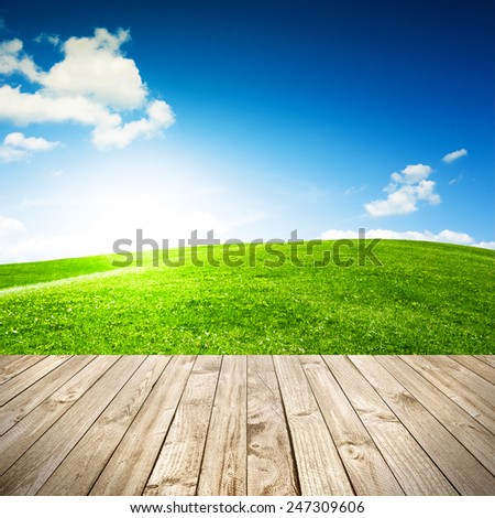 Wood terrace and perspective view on forest field or green hill - stock photo