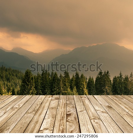 Wood terrace and perspective view on forest mountains - stock photo