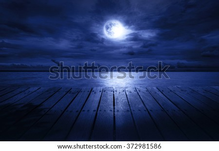 wood terrace for night relax by see the nice full moon  - stock photo