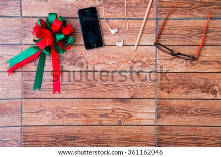 Wood texture mock up with ribbon, smart phone, earphone, pencil and glasses. View from above. - stock photo