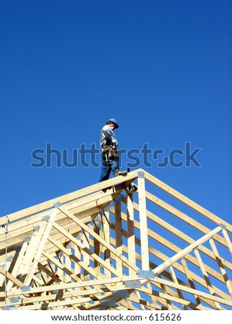 wood trusses against sky with a man standing on the top - stock photo