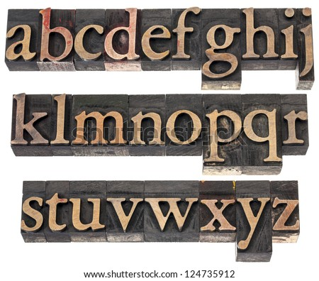 wood type alphabet in letterpress printing blocks stained by color inks, three rows isolated on white - stock photo