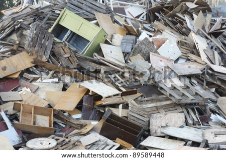 Wood waste in garbage dump waiting for wood chip production. Fuel for biomass boiler. - stock photo