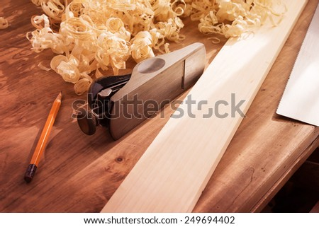 Wood working desk near the window with incandescent lighting, Wood working tools and wood shavings. Intentionally shot with low key shadows and shallow depth of field. - stock photo
