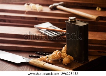 Wood working or carpentry scene with old tin solvent can in front. Shallow depth of field. Intentionally shot with low Key shadows. - stock photo