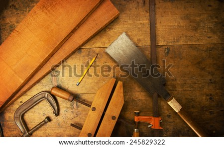 Wood working table. Saw, clamps and wood shavings on a work desk under incandescent light. - stock photo
