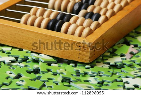 wooden abacus on pile of green puzzle