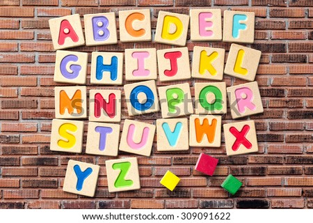 Wooden alphabet blocks with letters on brick wall  - stock photo