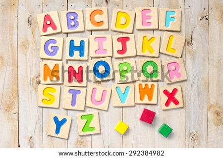 Wooden alphabet blocks with letters on wood background - stock photo