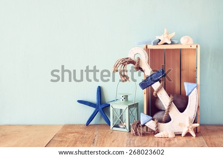 wooden anchor, star fish and lantern on wooden table. vintage filtered image  - stock photo