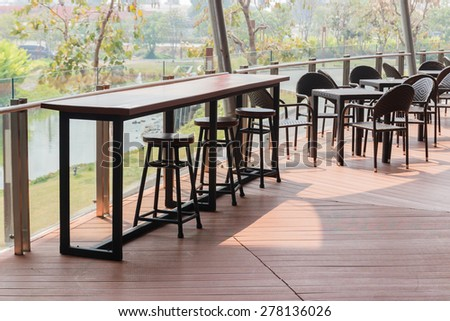 wooden and rattan chair and table on the terrace - stock photo