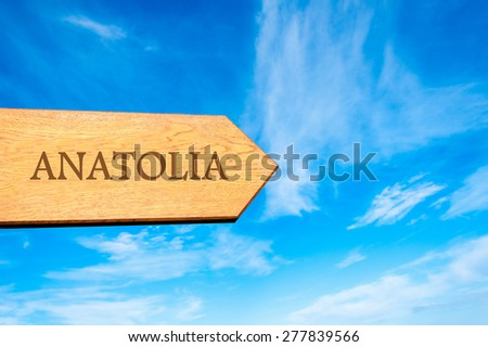 Wooden arrow sign pointing destination ANATOLIA, TURKEY against clear blue sky with copy space available. Travel destination conceptual image - stock photo