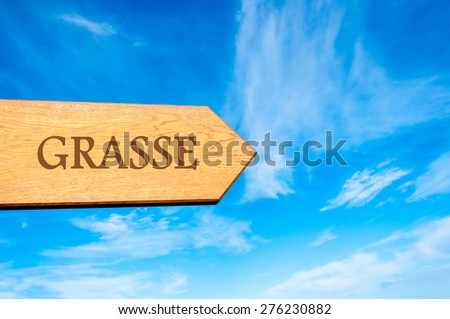 Wooden arrow sign pointing destination GRASSE, FRANCE against clear blue sky with copy space available. Travel destination conceptual image - stock photo
