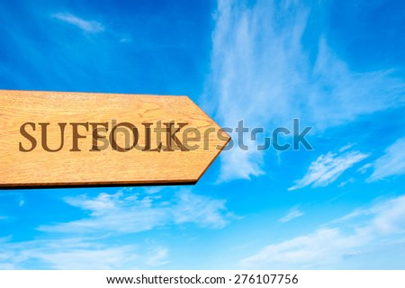 Wooden arrow sign pointing destination SUFFOLK, ENGLAND against clear blue sky with copy space available. Travel destination conceptual image - stock photo
