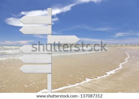 wooden arrow signboard on tropical beach - stock photo