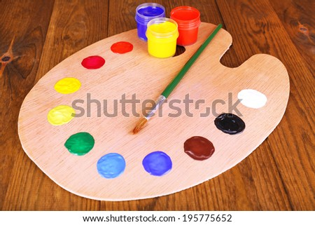 Wooden art palette with paint and brush on table close-up