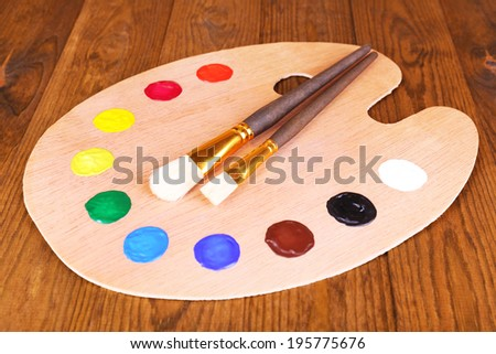 Wooden art palette with paint and brushes on table close-up - stock photo