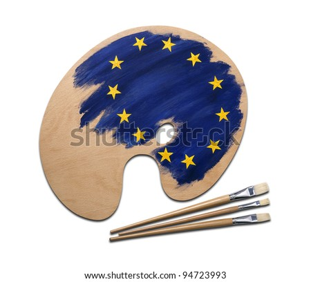 wooden artists palette loaded with european flag paints and brush, isolated on a white background with clipping path. - stock photo