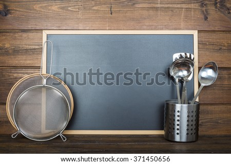 Wooden background with an ampty chalkboard with a space for text and some cooking utensils - stock photo