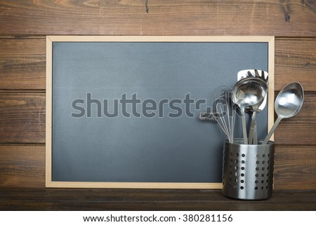 Wooden background with an empty chalkboard with a space for text and some cooking utensils - stock photo