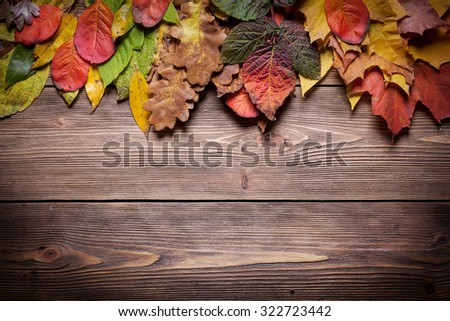 Wooden background with autumn leaves - stock photo