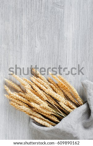 Wooden background with bunch of wheat in the linen napkin