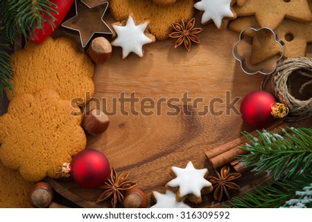 wooden background with Christmas cookies and ingredients for baking, top view