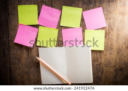 Wooden background with eight blank colorful sticky notes and notebook and pencil - stock photo