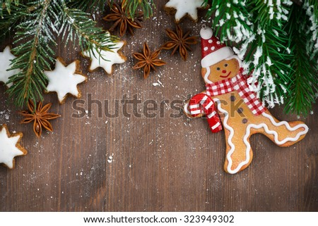 wooden background with fir branches, cookies and gingerbread man, horizontal, top view, close-up - stock photo
