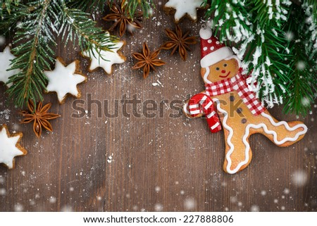 wooden background with fir branches, cookies and gingerbread man, snow bokeh, top view - stock photo