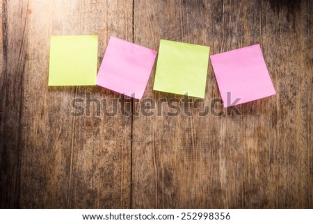Wooden background with four blank colorful sticky notes - stock photo