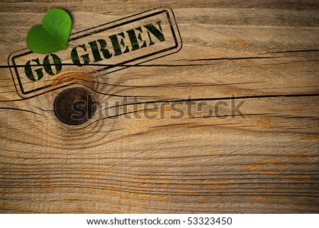wooden background with green natural heart and go green message - stock photo
