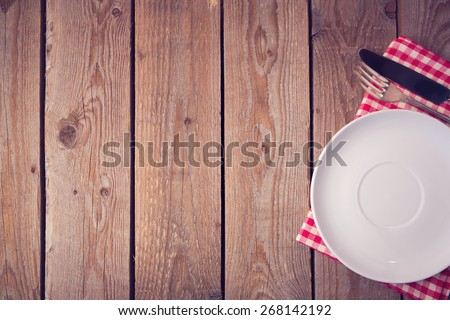 Wooden background with plate and silverware. View from above - stock photo