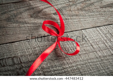 Wooden background with red bow and ribbon with copy space - stock photo