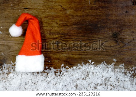 Wooden background with santa cap, snow on the border and copyspace for your Christmas text - stock photo