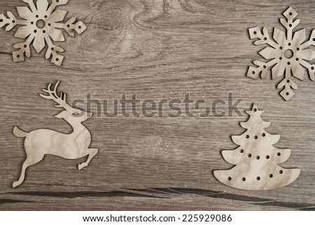 Wooden background with snowflakes, raindeer and Christmas trees. Space for your text