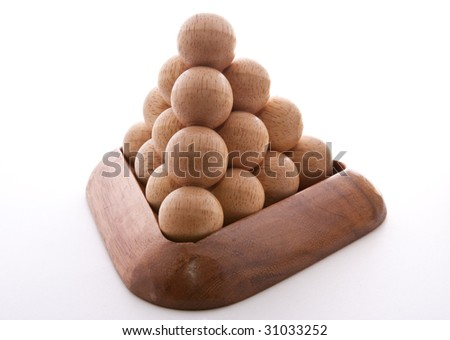 Wooden balls puzzle assembled on white background - stock photo