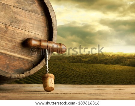Wooden barrel and corkscrew close up with vineyards and rural landscape on background.