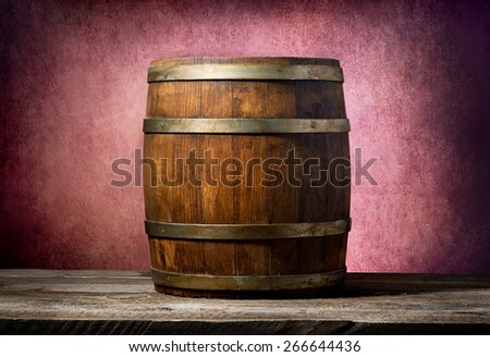 Wooden barrel on a table and pink background - stock photo