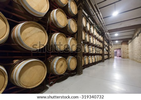 wooden barrels in rows at contemporary winery factory  - stock photo