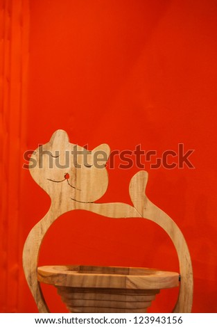 Wooden basket decorated with cat handle isolated on red background. - stock photo