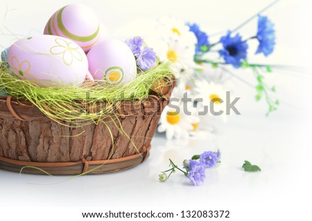 wooden basket of easter eggs with wildflowers