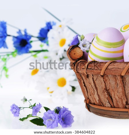 wooden basket of easter eggs with wildflowers - stock photo