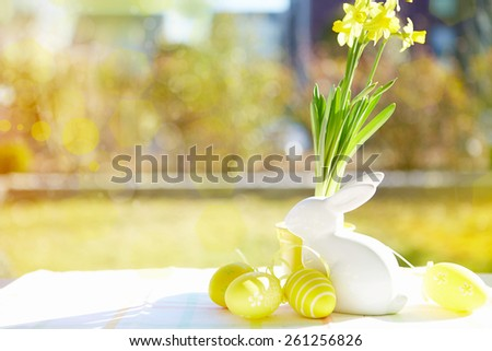 wooden basket with colorful easter eggs and a rabbit on wooden table - stock photo