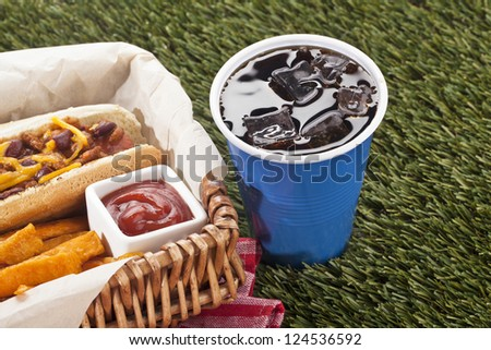Wooden basket with hotdog sandwich, fries and ketchup dip beside a cup of ice old cola - stock photo
