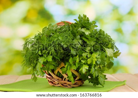 Wooden basket with parsley and dill on wooden table on natural background - stock photo