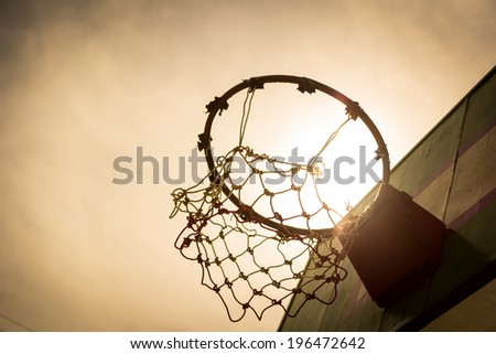 Wooden basketball hoop during sunset. - stock photo